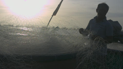 Guy Folds Fishing Net into Boat after Hurricane Closeup Live Action