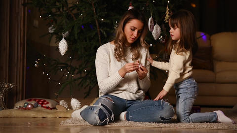 Mom and the girl are looking at a Christmas tree under a Christmas tree Footage