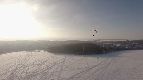 aerial view. Competitions pilots paragliding on a frozen lake near the city park Footage
