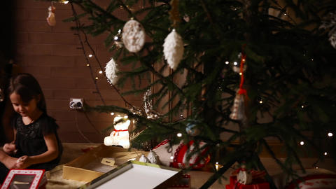 Mom and her daughter sit under a decorated Christmas tree at home consider gifts Footage