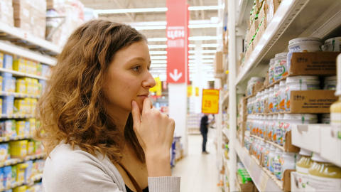 A young girl takes the baby food in the store, 4k Footage