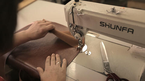 Woman sews new leather case for couch behind sewing machine Archivo