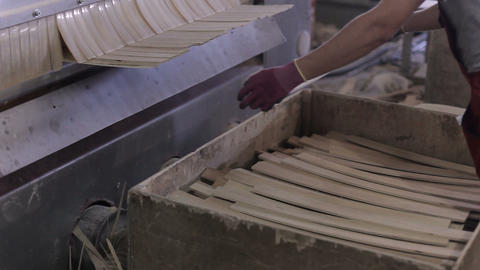 equipment in the furniture factory. worker cuts plywood into slats Footage