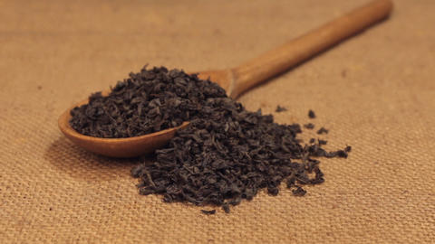 Approximation of a wooden spoon overflowing with dried black tea leaves, lying Footage