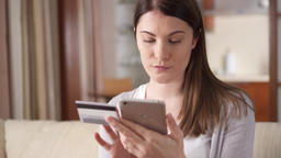 Businesswoman sitting on sofa in living room buying online with credit card on Footage