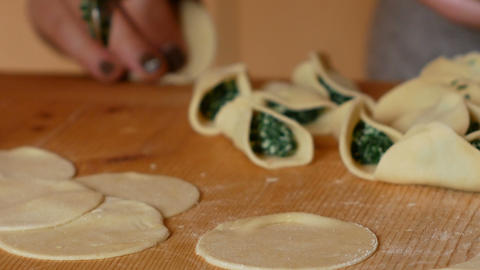 Elderly woman fills ravioli with spinach in a skillful way Footage
