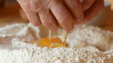 elderly woman pours the egg on the flour Footage