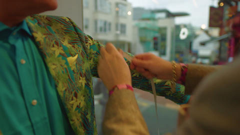 Man on colourful suit gets arm measured at the tailors Archivo