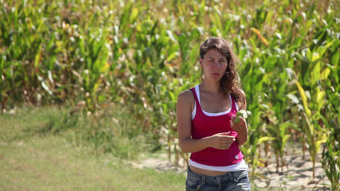 Beautiful girl eating an apple by a corn field Footage