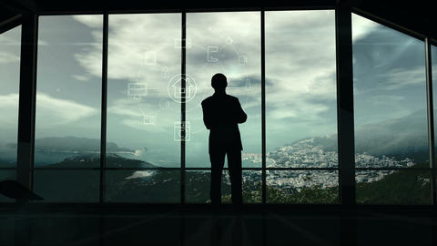 A man is standing by the window viewing IOT infographics... Stock Video Footage