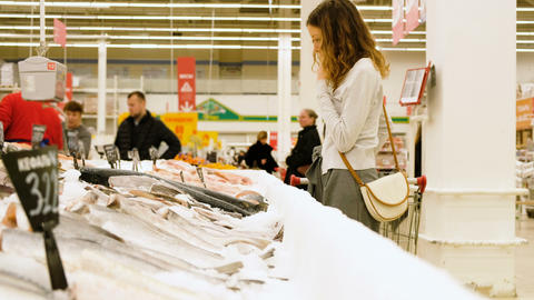 A girl chooses a fish in a fish department in a supermarket, 4k Live Action