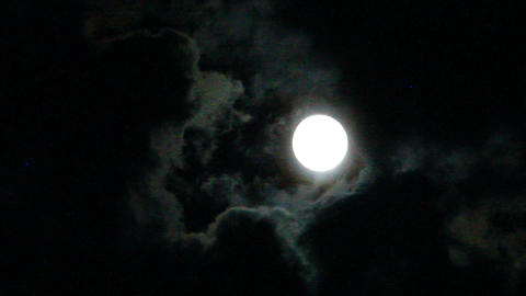 Moon glows through the dark night clouds Footage