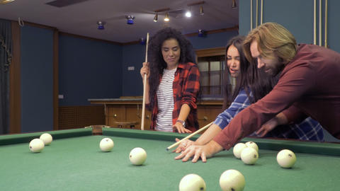 Young man teaches his friends to play billiard Footage