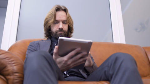Adult caucasian man sits on sofa and uses digital tablet Footage
