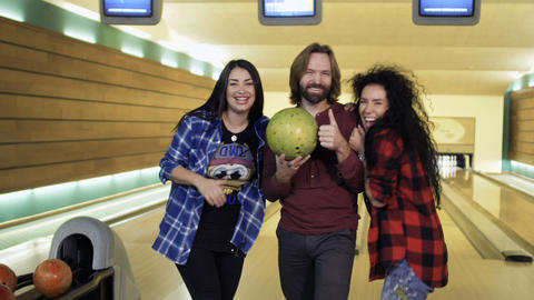 Three caucasian friends shows thumbs up standing at bowling alley Footage