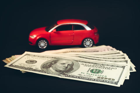 A car on a background of large bills of dollars フォト