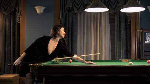 Beautiful brunette in sexy dress plays billiard Footage