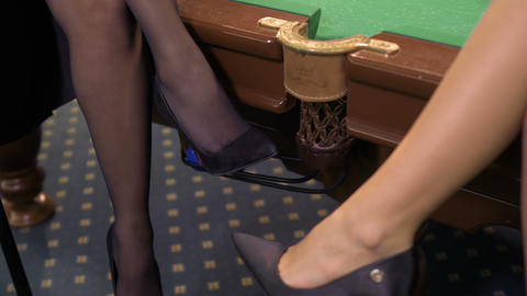 Women with sexy legs and on high heels sits at billiard table Footage
