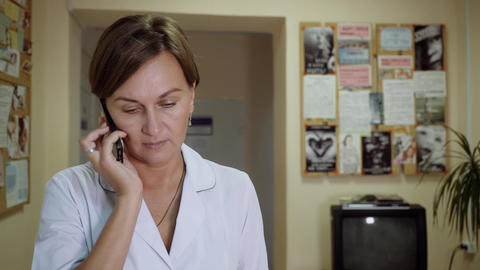 A female doctor walks down the corridor and talks on the phone Filmmaterial