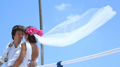 bride and groom stand on a strong wind at the wedding day near the sea. Veil Footage