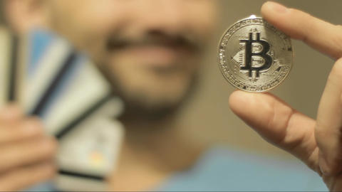 man holds bitcoin and credit cards Live Action