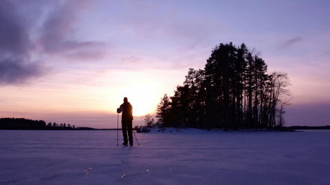 Tour skater at a frozen lake ice during sunset Footage