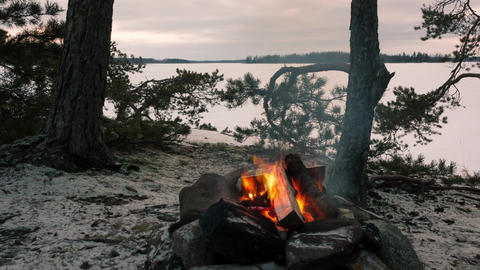 Campfire in darkening night by a frozen lake time-lapse Footage