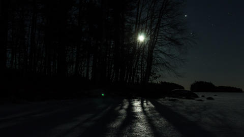 Moon rising time-lapse by a frozen lake Footage
