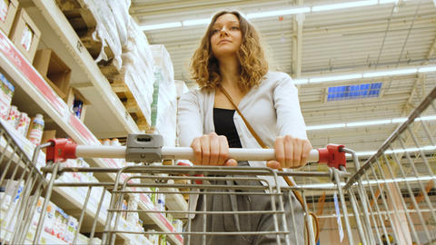 Woman walking with shopping cart in 4K Footage