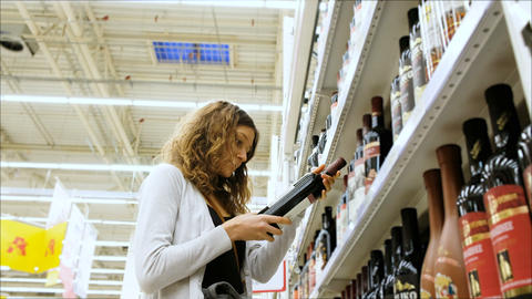 Woman chooses wine in a supermarket, 4K Footage