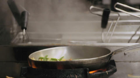 Chef is stirring vegetables in a pan Footage