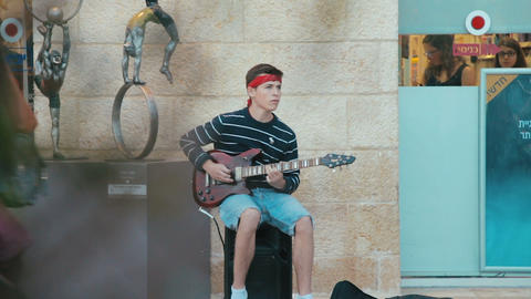 Jerusalem, Israel - May 11, 2017: Young street musician guitarist play music Footage
