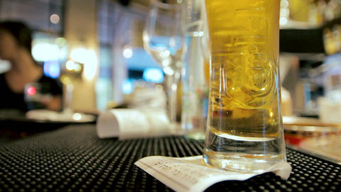 Glass of beer placed on the counter in a cafe. Waitress takes the glass Footage