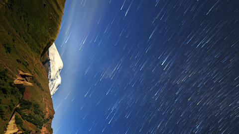 Vertical video. Stars draw fading lines and clouds over Mount Elbrus. Night Footage