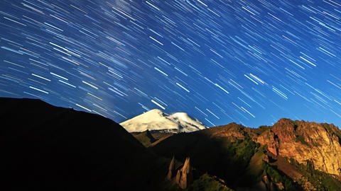 Stars draw lines and clouds over Mount Elbrus. Night landscape. Russia Footage