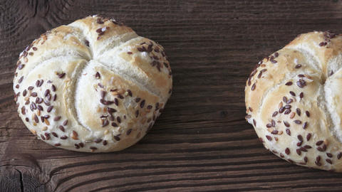 Tasty freshly baked kaiser rolls with seeds on wooden board Footage