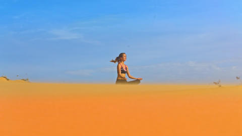 Wind Shakes Girl Hair Meditating on Sand in Sky Background Footage