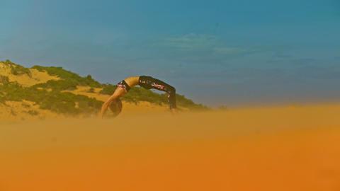 Girl Holds Yoga Pose among Desert under Scorching Sun Image