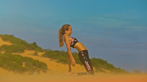 Girl Sits in Yoga Pose in Breeze among Endless Dune Closeup Image