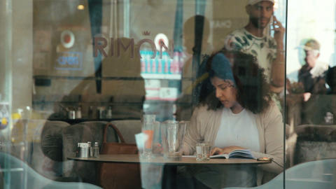 Jerusalem, Israel - May 11, 2017: Woman sitting in cafe Rimon. She writes notes Footage