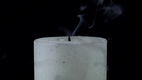 White candle is extinguished on a black background Footage
