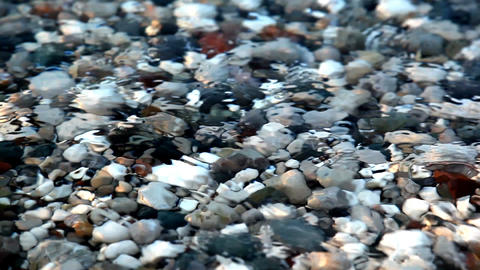 Shot in HD with macro focus on pebbles as surf washes over beach at sunset.High  Footage