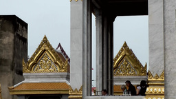 Thailand Bangkok 018 medium shot, magnificent roofs of temple behind pillars Footage