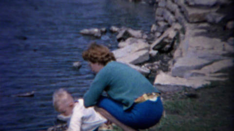 1962: Mother baby enjoy lakeshore water summer rock throwing Footage