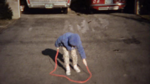 1963: Girl confidentially jumps rope in driveway garage door open Live Action