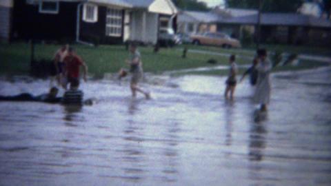 1961: Suburban flood street kids splashing in toxic wastewater Live Action