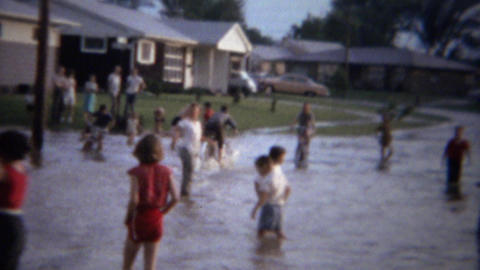 1961: Kids riding bike thru flooded street in stagnant sewage water Footage