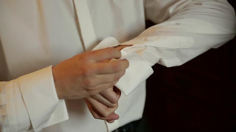 The bridegroom is wearing a wedding shirt, a tie, a jacket Live Action