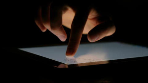 Hand draws words with a finger on the tablet in the dark close up, 4k Live Action