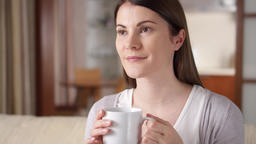Young woman relaxing on couch at home. Pretty female drinking coffee or tea from Footage